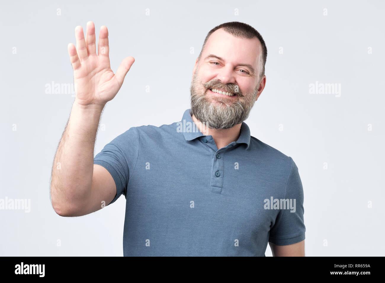 Polite ymature man with beard dressed in denim shirt saying hi, waving with hand - Stock Image