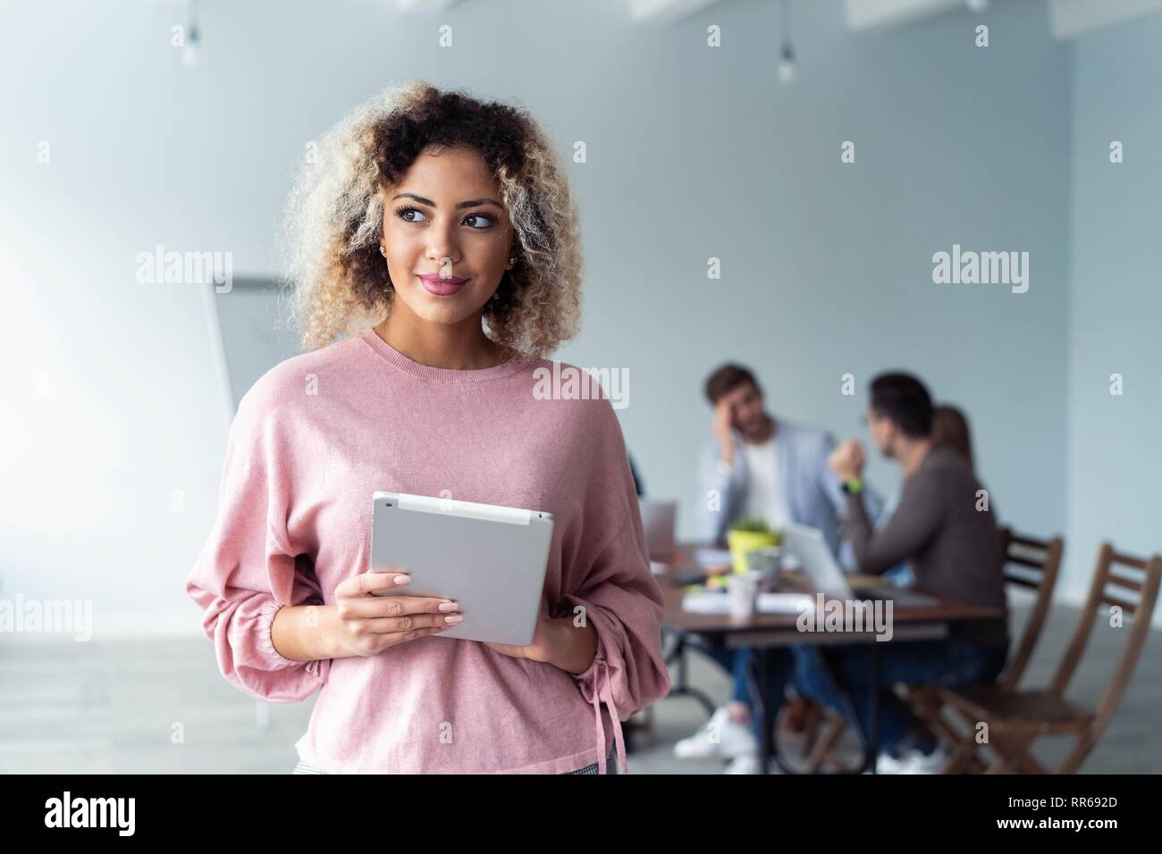 Business woman standing in foreground with a tablet in her hands, her co-workers discussing business matters in the background. - Stock Image