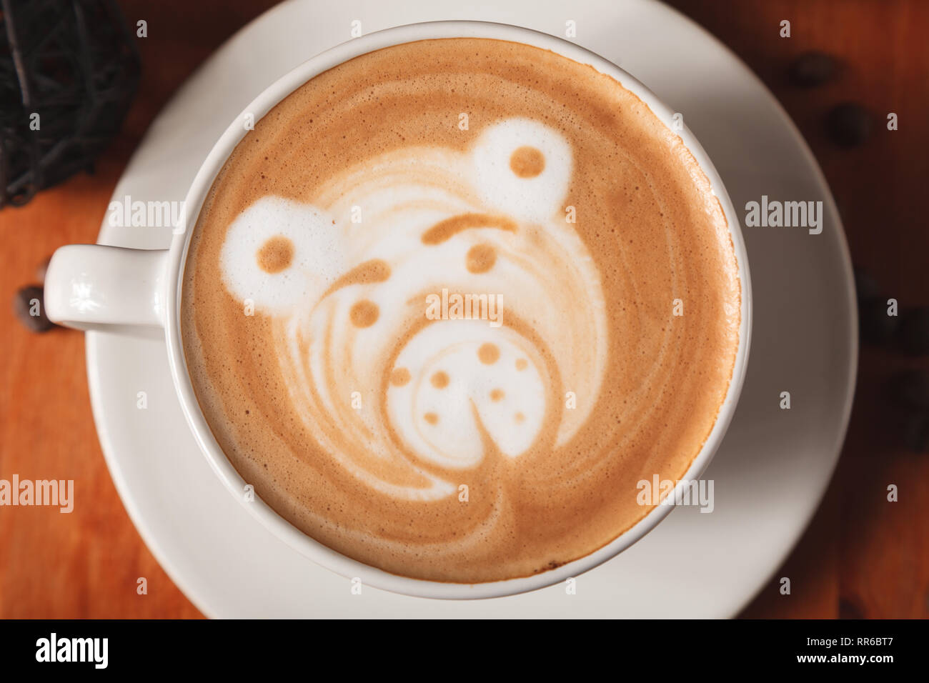 White Cup cappuccino coffee with a latte-art pattern in the form of a bear close-up on a wooden background. The concept of making coffee in a coffee s - Stock Image