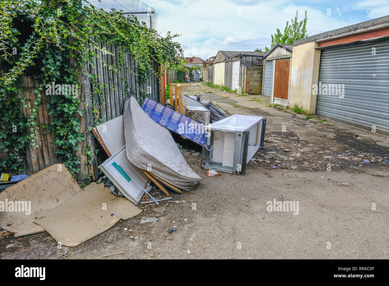 Large pile of rubbish, rotting after being fly tipped and left in an urban alleyway. Demonstrates anti-social behaviour. - Stock Image
