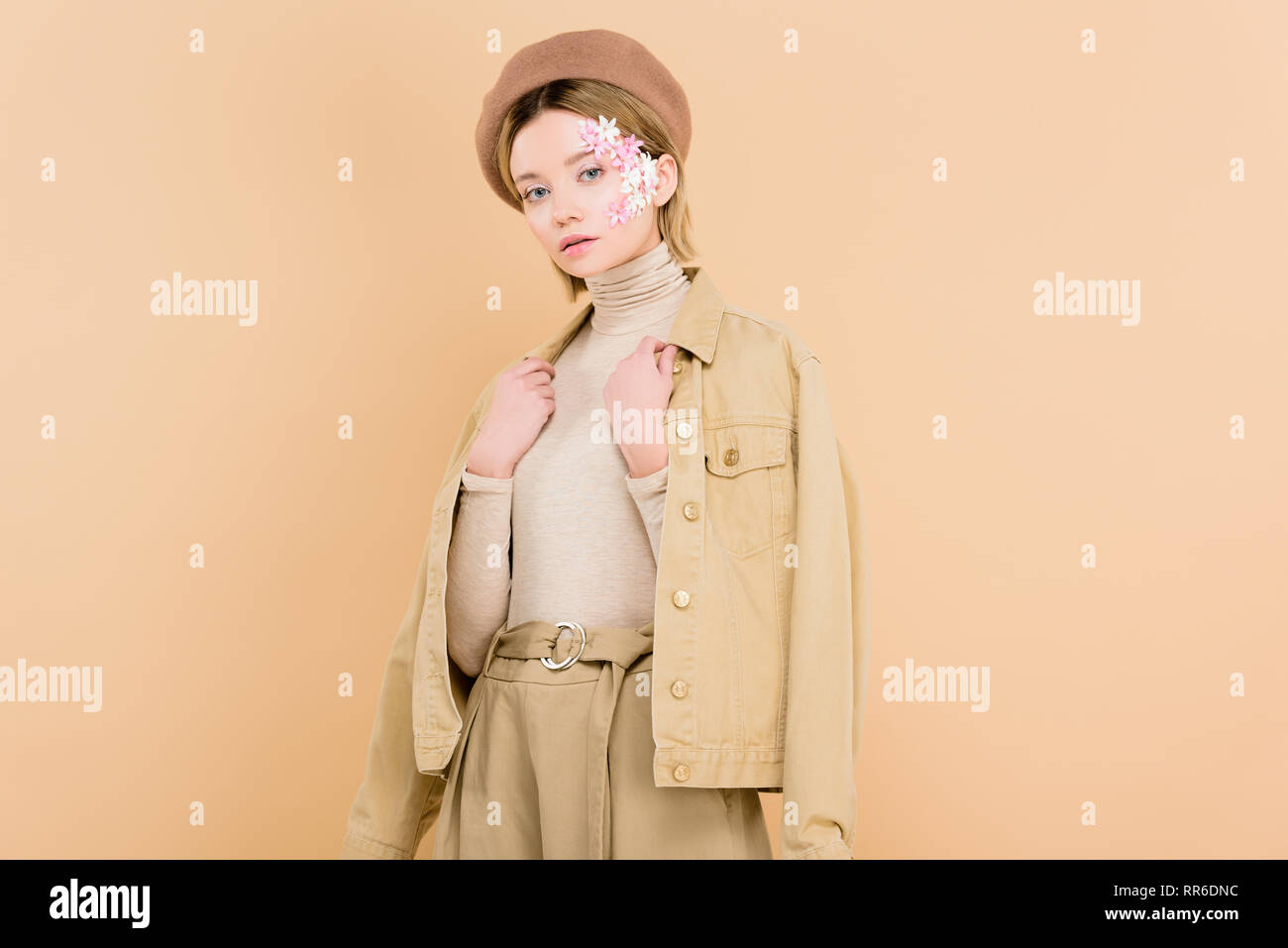 bc214c077e7c8 woman with flowers on face wearing beret and standing isolated on beige -  Stock Image