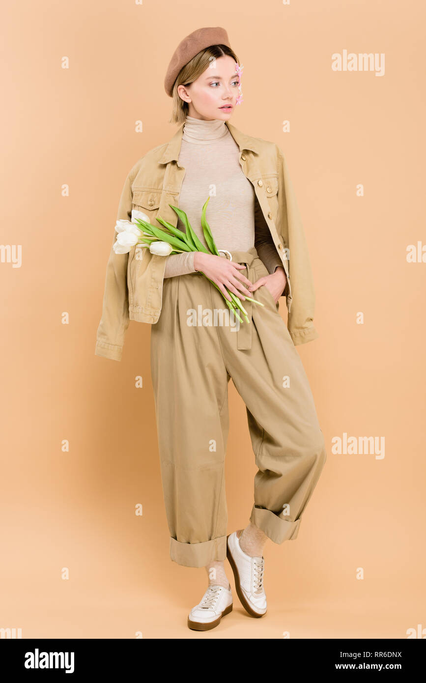 54e3076529f10 trendy woman wearing beret and holding bouquet isolated on beige - Stock  Image