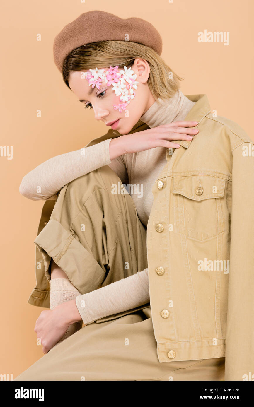 2a35326d1fda8 trendy woman with flowers on face wearing beret isolated on beige - Stock  Image