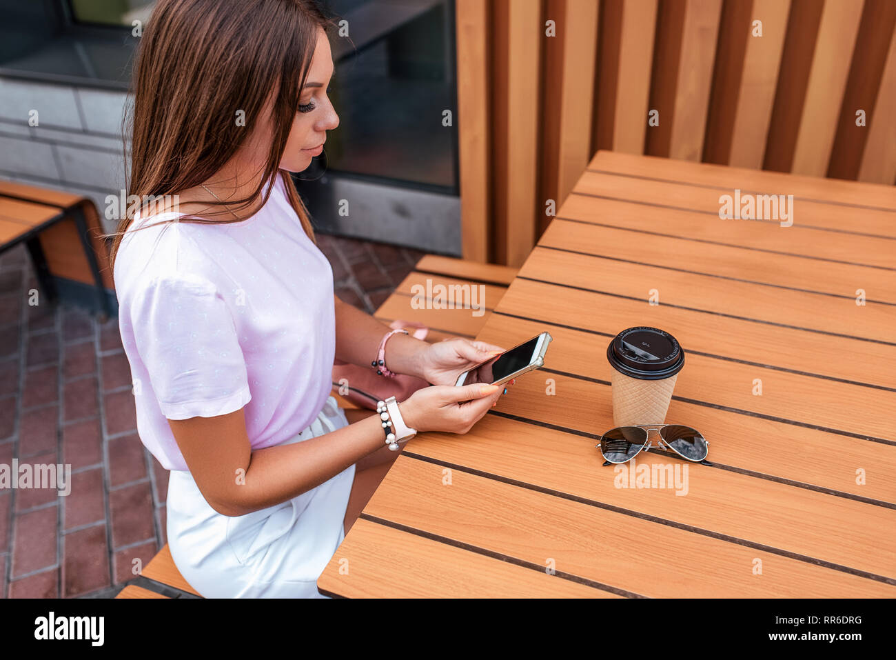 Beautiful girl cafe table in summer city. In hands of smartphone, cup with coffee tea, solar buds. Social networks, online, correspondence on phone - Stock Image