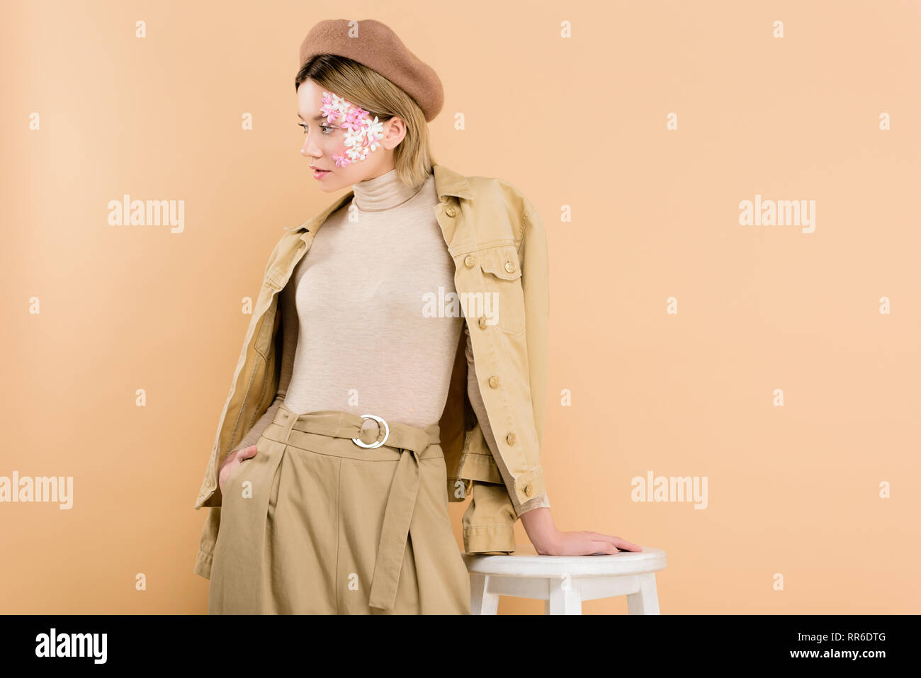 8adb38a007d7a stylish woman in beret standing near chair isolated on beige - Stock Image