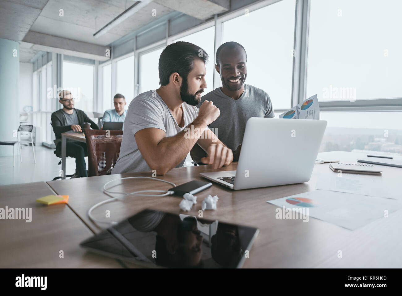 Two young businessmen using laptop and discussing new project at office, developing strategy for online business, explaining sharing ideas, preparing presentation, having brainstorming session - Stock Image