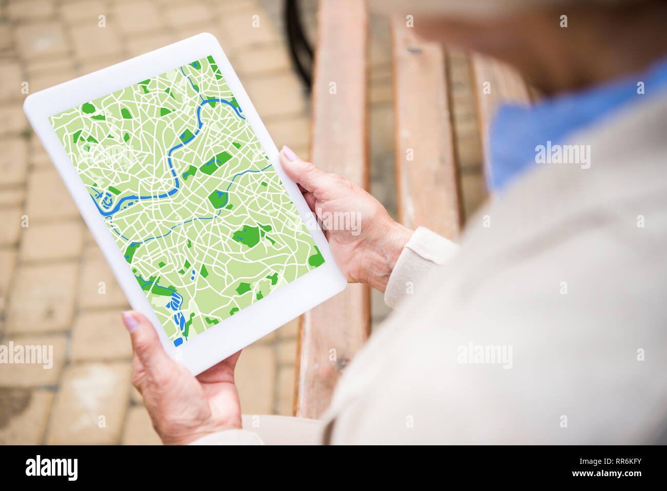 selective focus of senior woman using digital tablet with map on screen Stock Photo