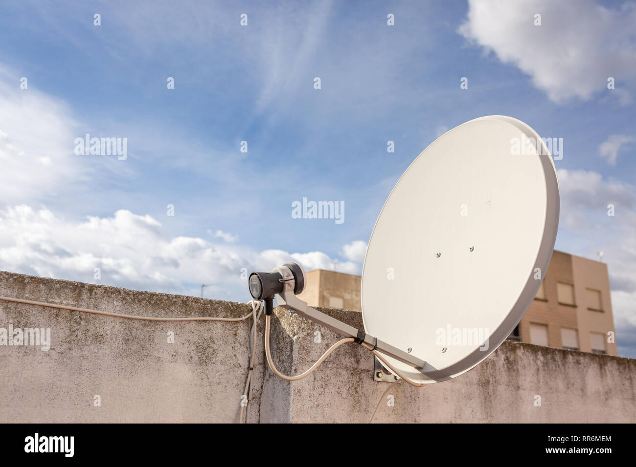 Old satellite dish on apartament building in Spain. Sunny nice day. - Stock Image