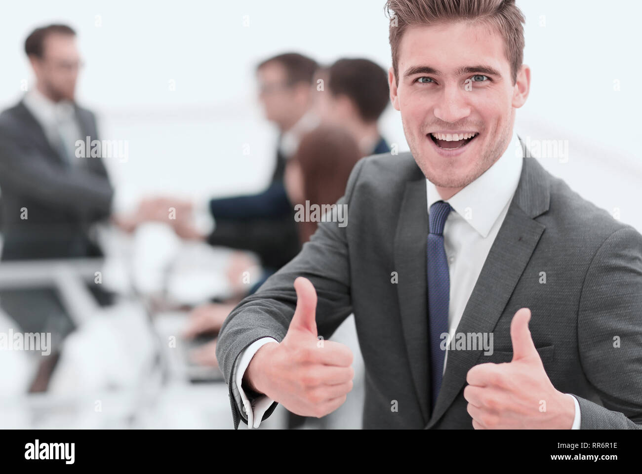 Portrait of happy energetic businessman with thumbs up while  co - Stock Image