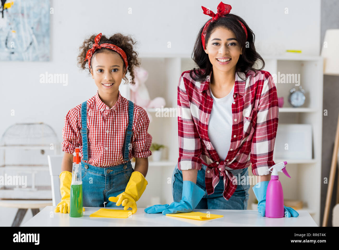 happy african american mother with adorable daughter in bright rubber gloves and spray bottles cleaning house - Stock Image