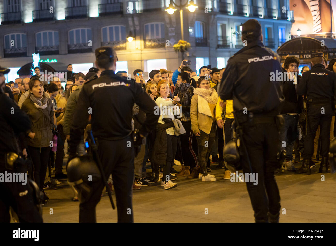 Madrid, Spain. 24th Feb, 2019. Clashes between supporters of Maduro and the opposition took place in Madrid. The origin of the dispute was a demonstration organized by the supporters of Maduro at Puerta del Sol to protest against the intervention of Spain in Venezuela. Venezuelan citizens of the opposition showed up and the intervention of the police was necesary to avoid any stronger confrontations between both parts.  In the picture, the police blocking way of the people against Maduro to avoid further conflicts between both parties. Credit: Lora Grigorova/Alamy Live News - Stock Image