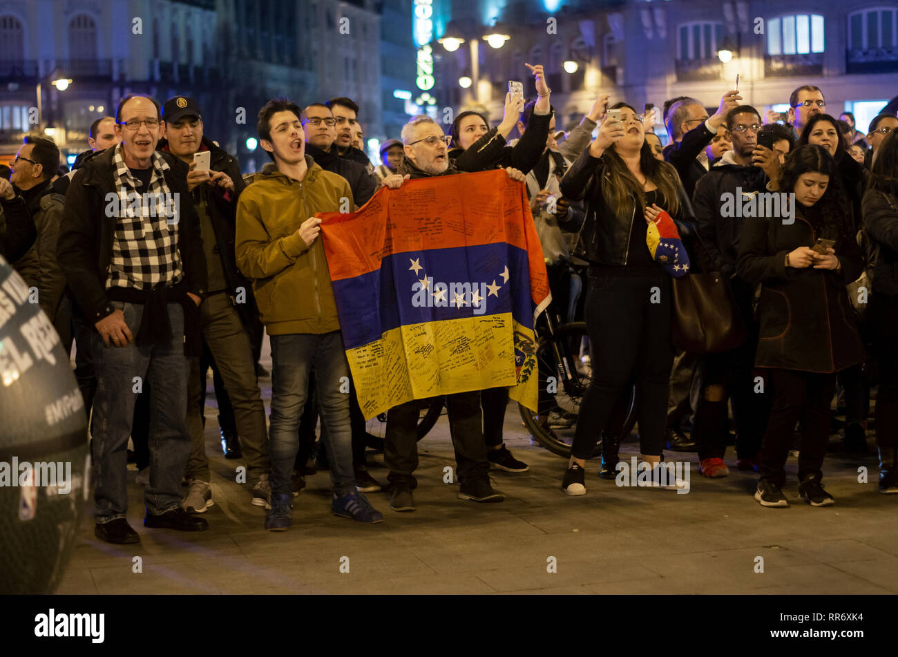 Madrid, Spain. 24th Feb, 2019. Clashes between supporters of Maduro and the opposition took place in Madrid. The origin of the dispute was a demonstration organized by the supporters of Maduro at Puerta del Sol to protest against the intervention of Spain in Venezuela. Venezuelan citizens of the opposition showed up and the intervention of the police was necesary to avoid any stronger confrontations between both parts.  In the picture, people protesting against Maduro holding the flag of Venezuela. Credit: Lora Grigorova/Alamy Live News - Stock Image