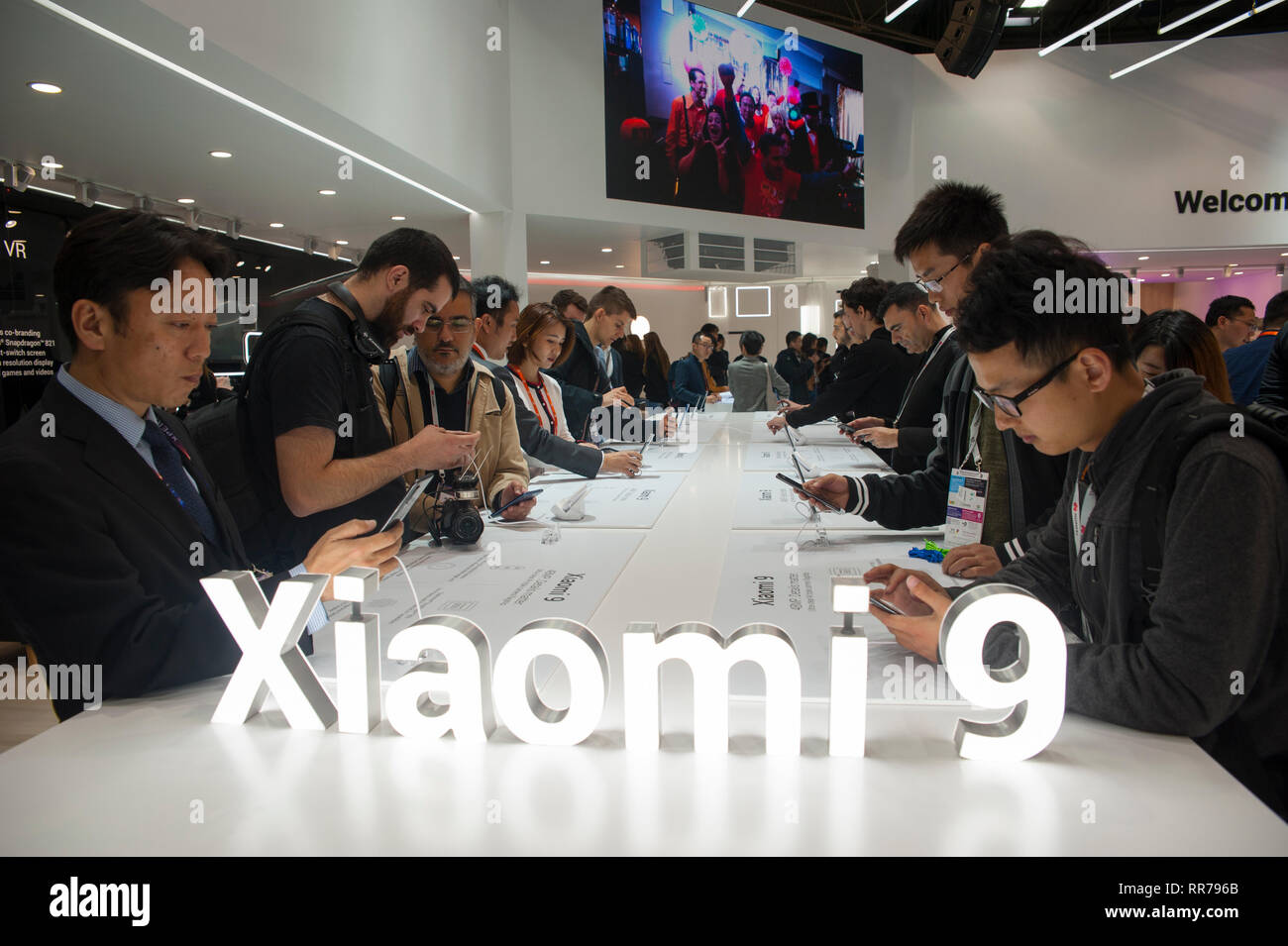 Barcelona, Spain, Monday, Feb. 25, 2019. Mobile World Congress attendees examine the new terminal of Xiaomi the Mi 9 with three cameras and integrated fingerprint reader on the screen is consolidated as the company's flagship for this 2019. The mobile congress will revolve around intelligent connectivity and address hyperconnectivity, 5G, the internet of things, artificial intelligence (AI) and big data. Credit: Charlie Perez/Alamy Live News Stock Photo