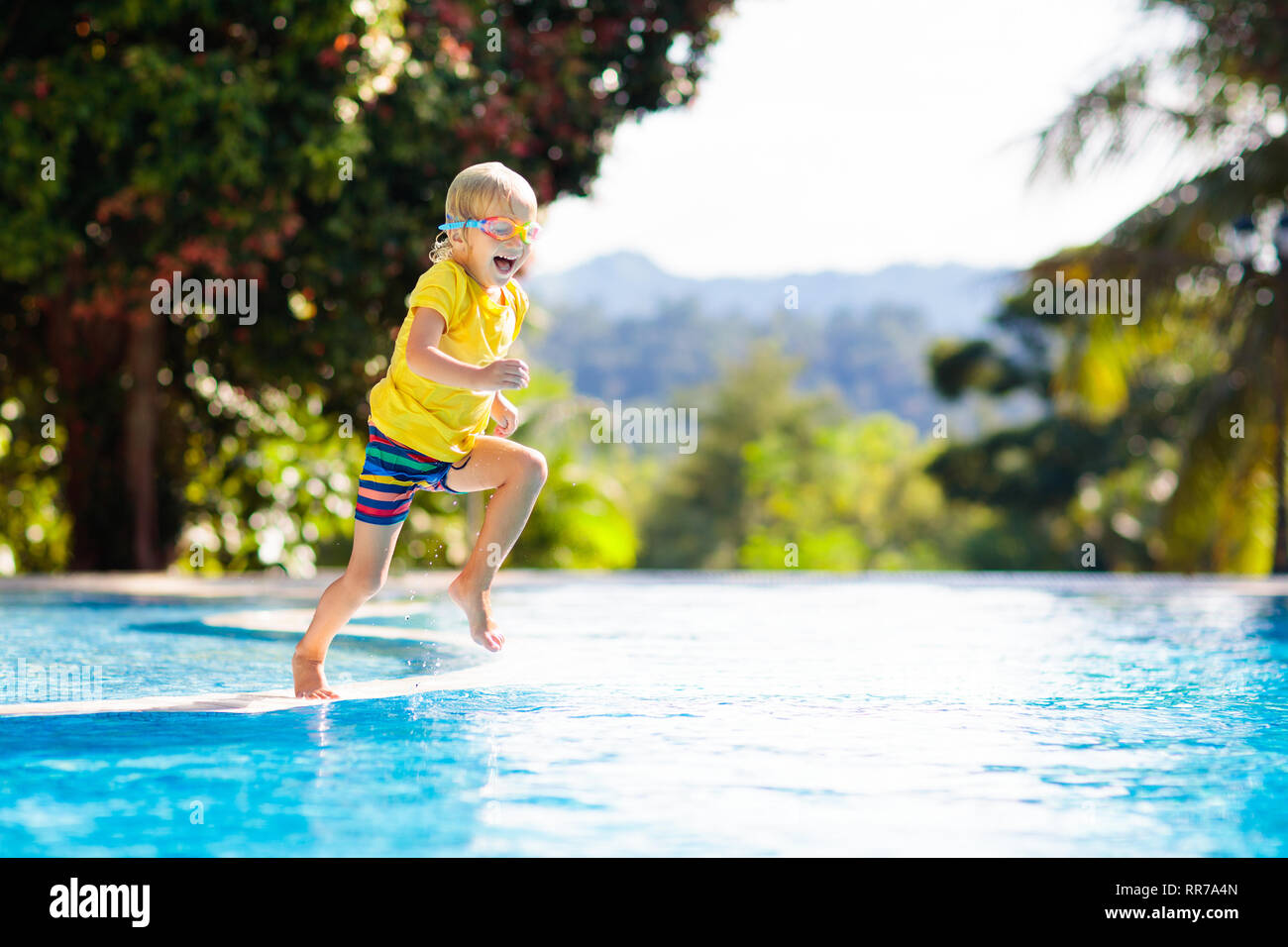 Child playing in swimming pool. Summer vacation with kids. Little boy jumping into water during exotic holiday in tropical island resort. Children swi - Stock Image