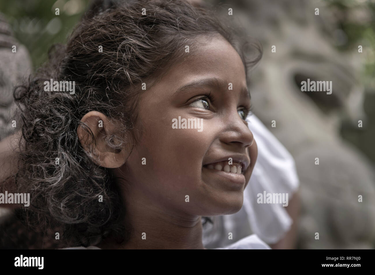A little girl takes time out from Sunday School at the Gangaramaya Buddhist Temple in Colombo Sri Lanka. - Stock Image