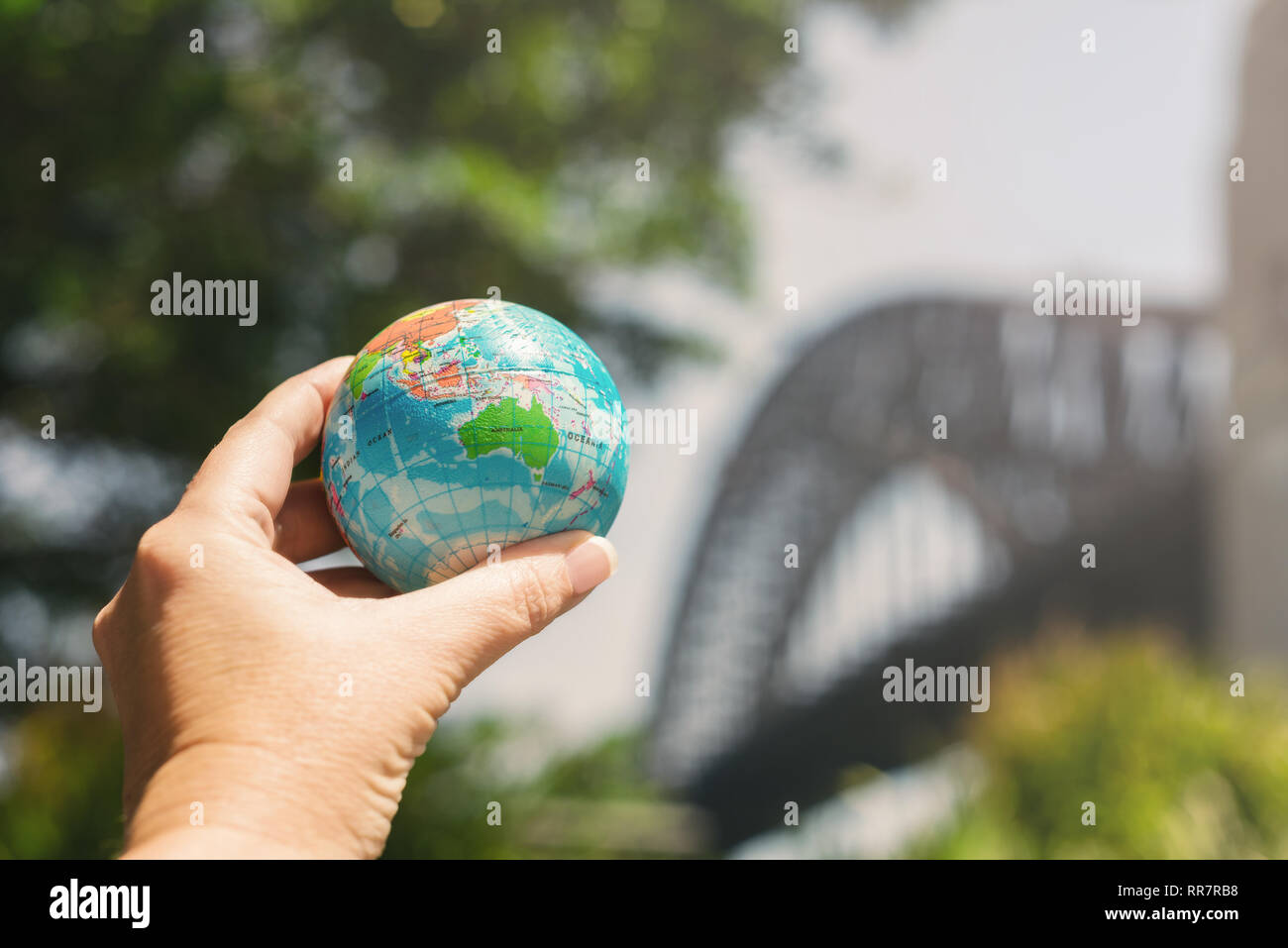 hand holding globe in front of famous Australian landmark Stock Photo