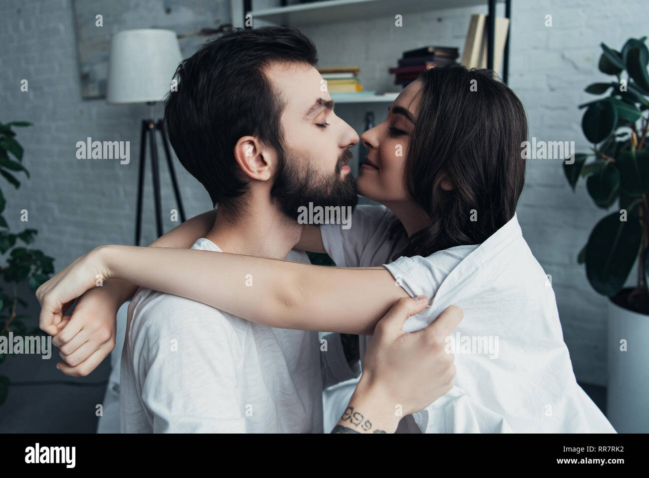 beautiful romantic young couple looking at each other and hugging at home - Stock Image