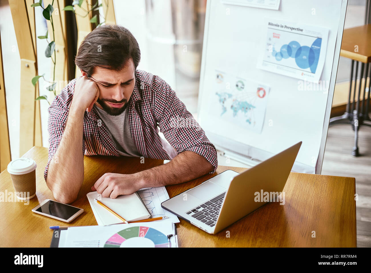 Bearded young man in casual sitting at his workplace and resting, head on arm. Portrait of a tired young businessman sitting at the table with laptop computer in despair. Modern office - Stock Image