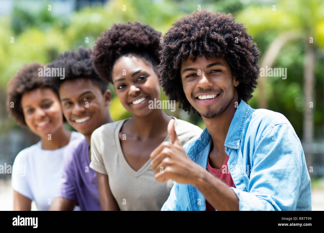 Happy african american man with group of young adults in line outdoor in city in summer - Stock Image