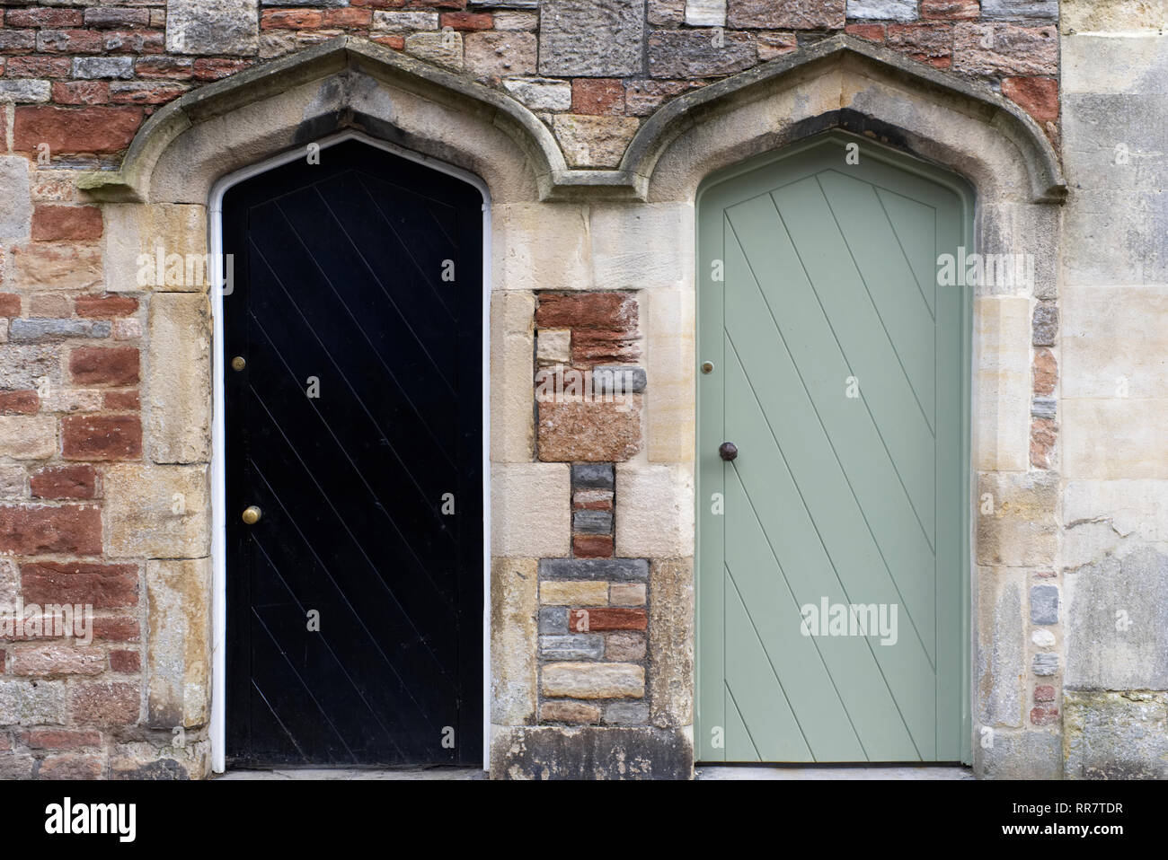 Almshouse terraced cottage and a traditional terraced stone cottage access doors. - Stock Image