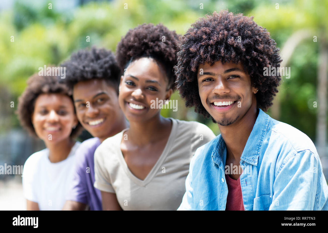 Handsome african american man with group of young adults in line outdoor in city in summer - Stock Image