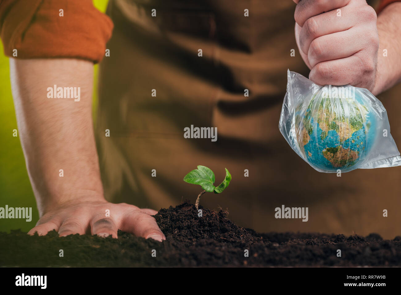 selective focus of man planting young plant and holding globe model in plastic bag on blurred background, earth day concept Stock Photo