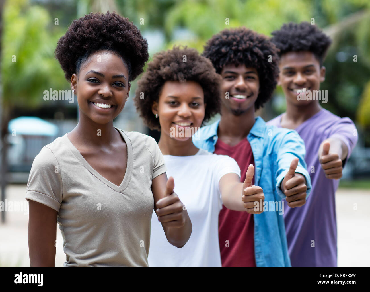 Group of african american young adults showing thumb up outdoor in the summer - Stock Image