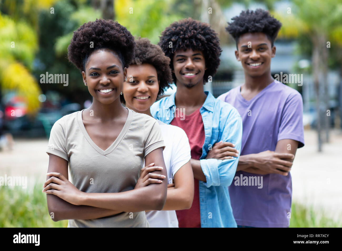 Group of african american young adults in line outdoor in the summer - Stock Image