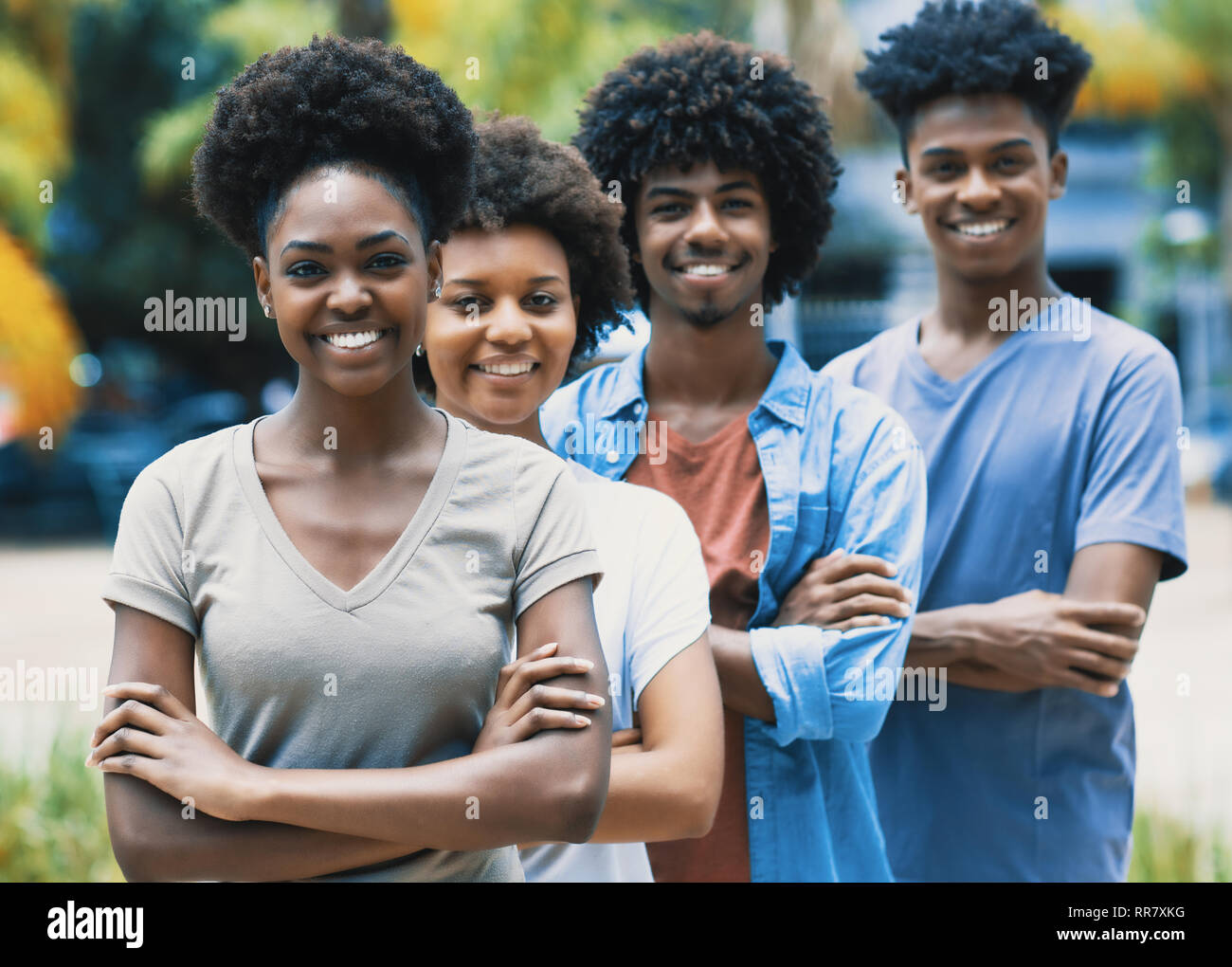 Happy laughing african american young adults in line outdoor in the summer - Stock Image