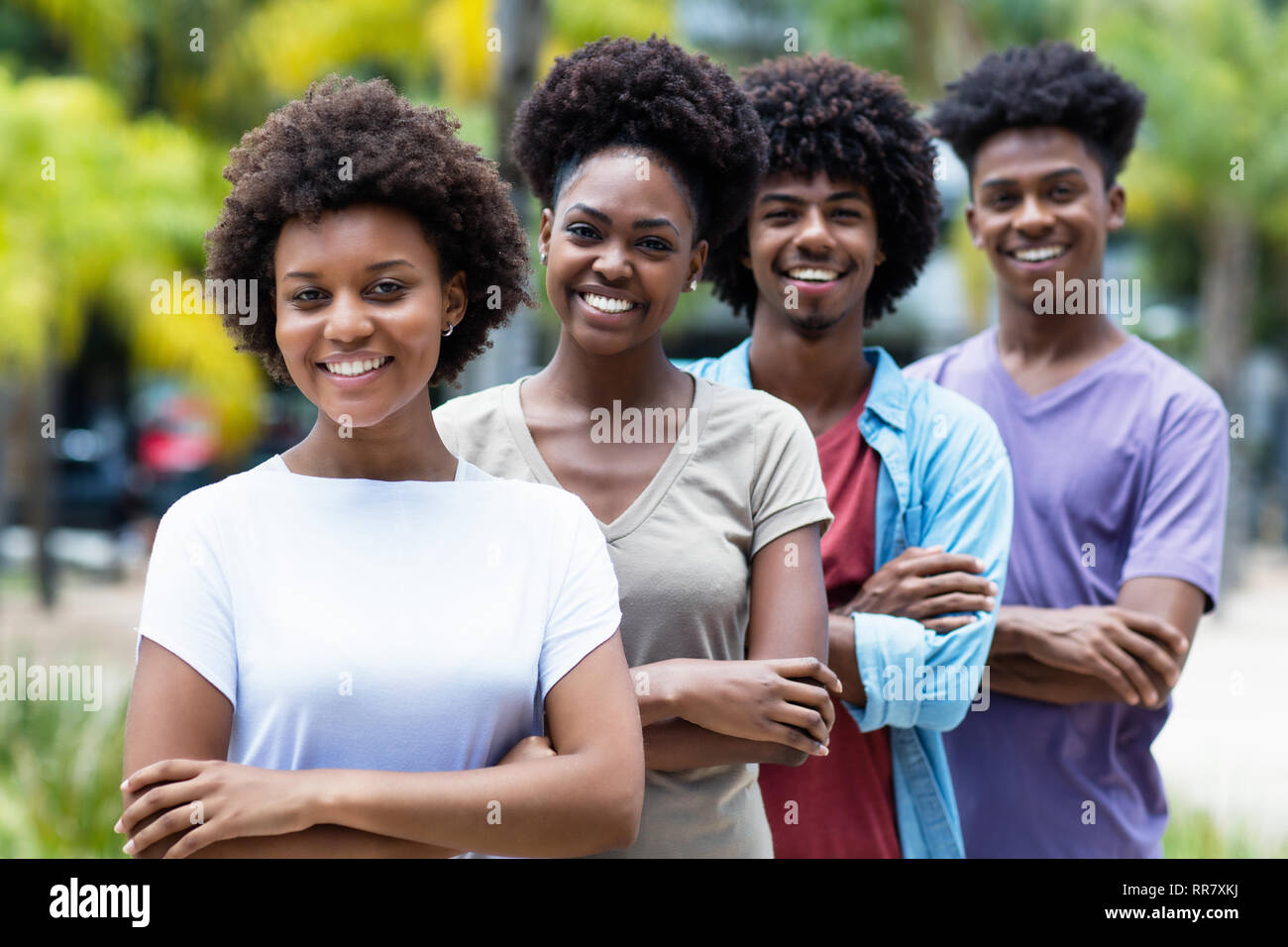 Group of african american young women and men in line outdoor in the summer - Stock Image
