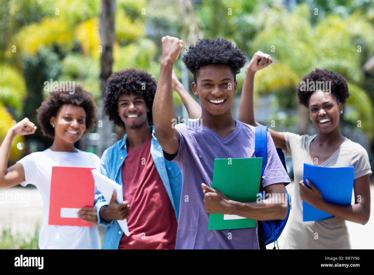 Cheering african male student with group of african american students outdoor in the summer - Stock Image