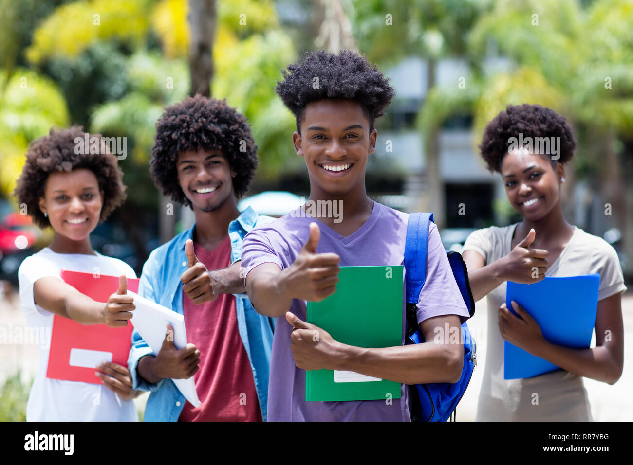 Successful african male student with group of african american students outdoor in the summer - Stock Image