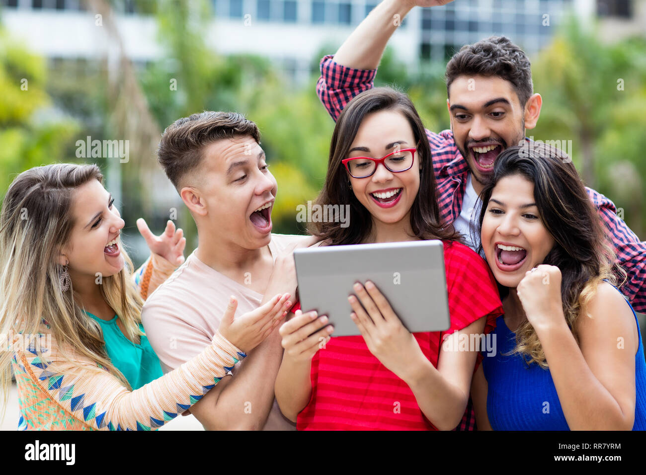 Laughing nerdy french female student with tablet computer and group of cheering international students outdoors in summer in the city - Stock Image