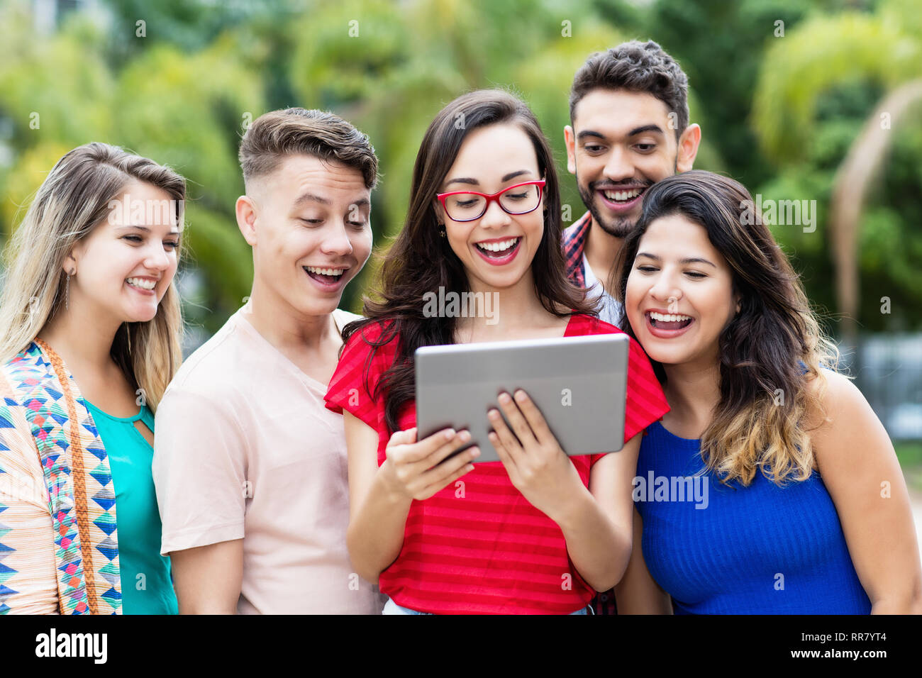 Nerdy french female student with tablet computer and group of international students outdoors in summer in the city - Stock Image