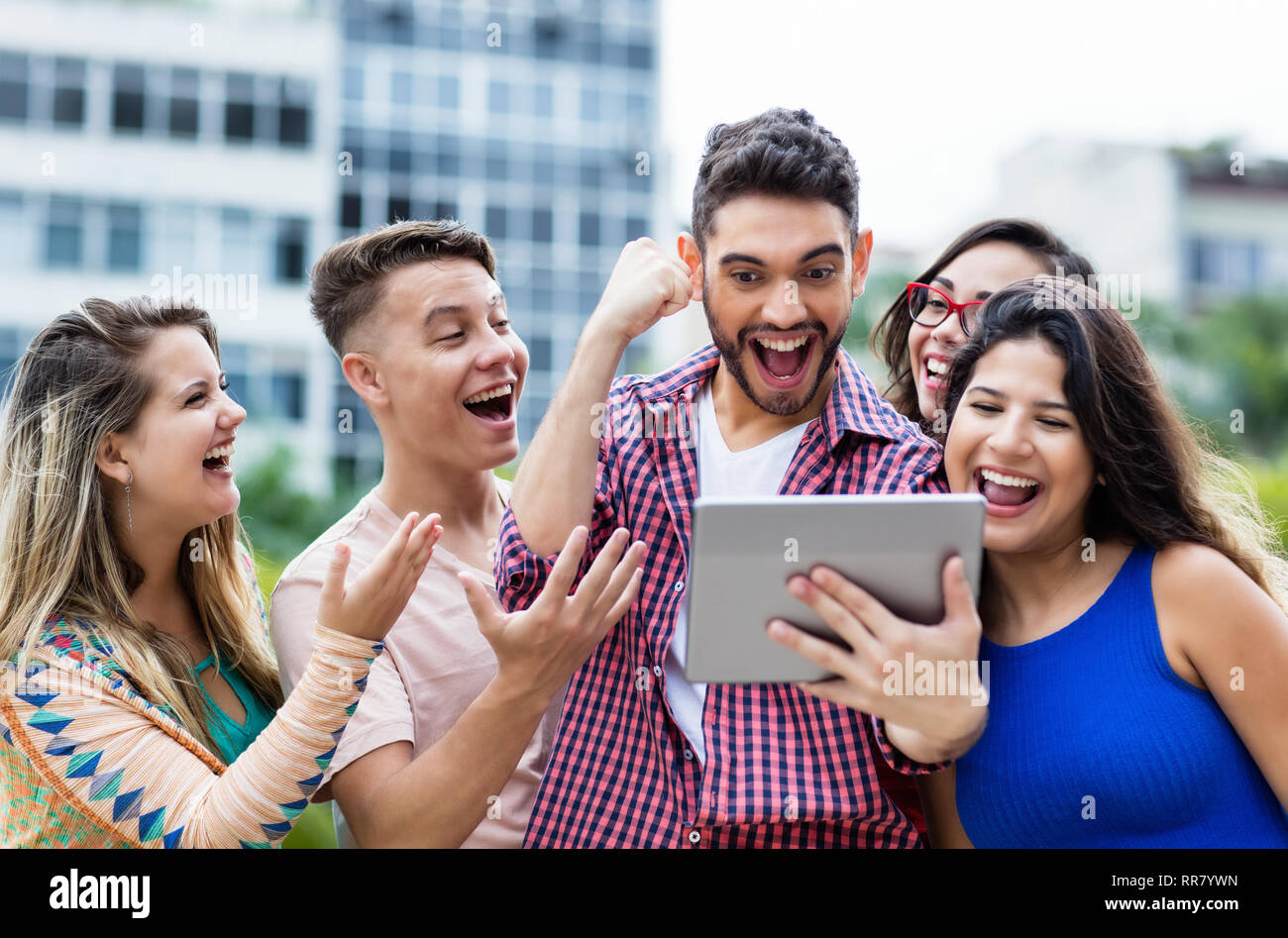 Cheering spanish hipster student with tablet computer and group of cheering international students outdoors in summer in the city - Stock Image
