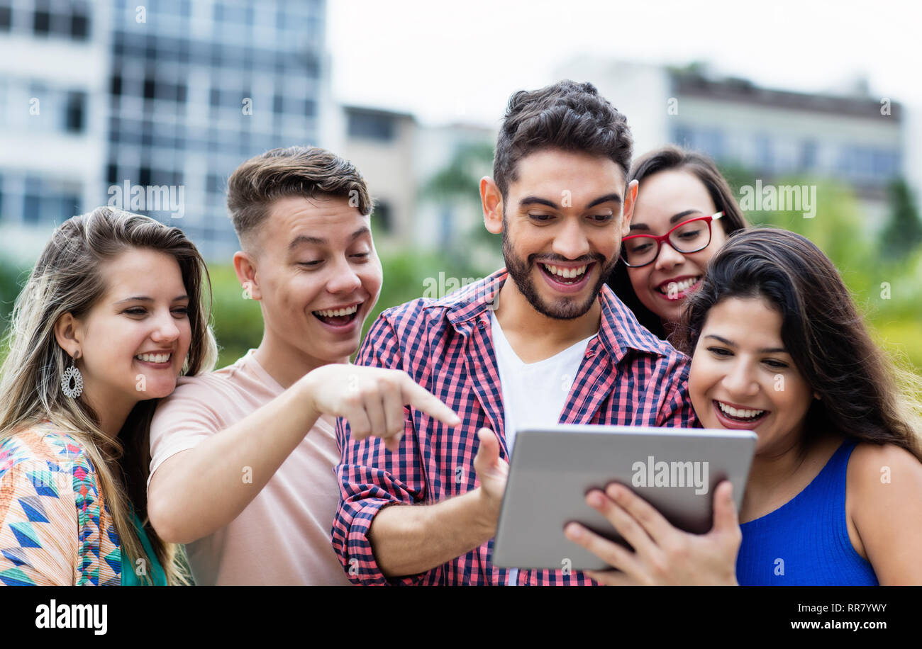 Spanish hipster student with tablet computer and group of cheering international students outdoors in summer in the city - Stock Image