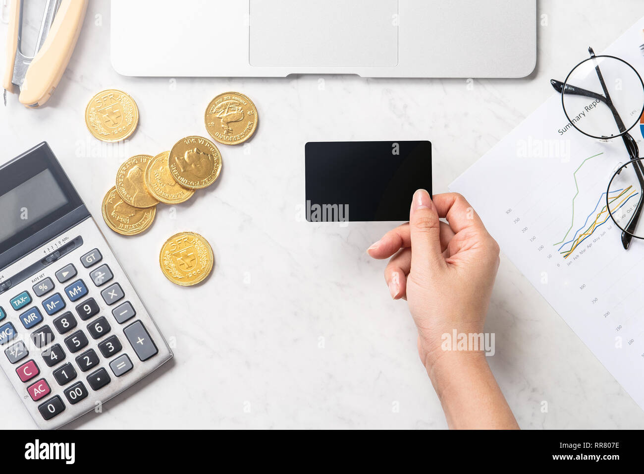 A woman is doing a online payment with card and smartphone isolated on a modern marble office table, mock up, top view, copy space, flat lay, lifestyl - Stock Image