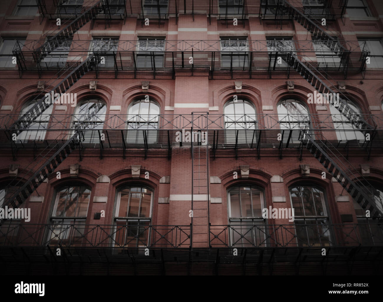 An apartment building in New York featuring fire escapes, arched keystone windows, ornamental railing  and symmetry. - Stock Image