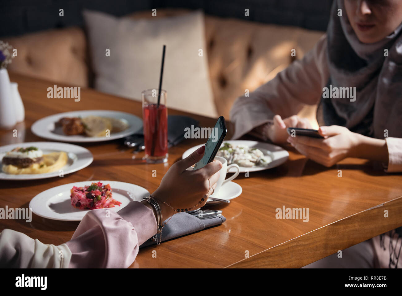 Two Muslim women sit with gadgets at a table in a restaurant - Stock Image