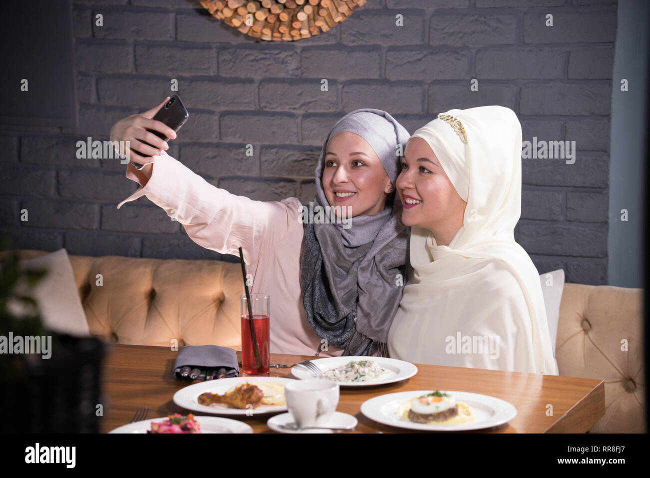 Two Muslim girl take a selfie at a table in a cafe - Stock Image
