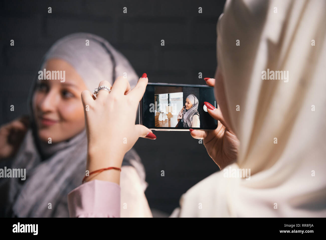 A girl takes pictures of her Muslim girlfriend in a cafe - Stock Image