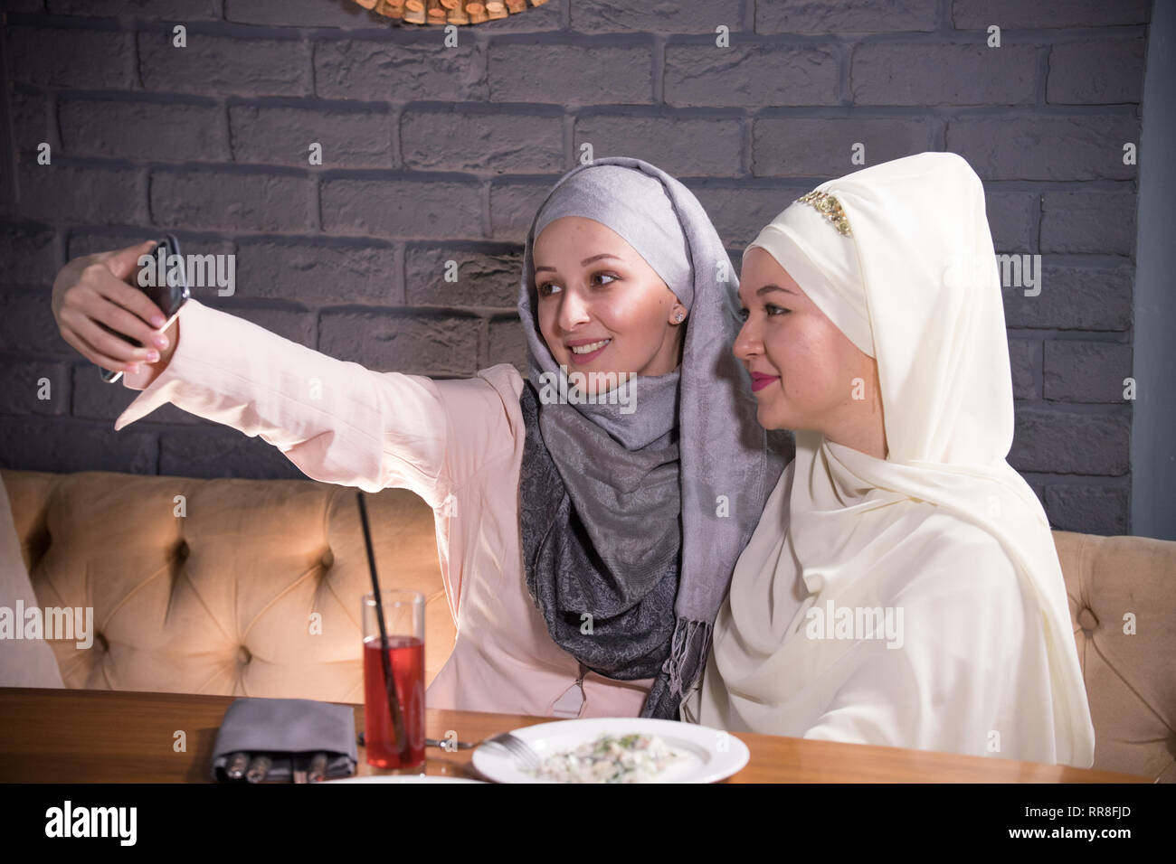 Girls in hijabs are photographed in a cafe - Stock Image