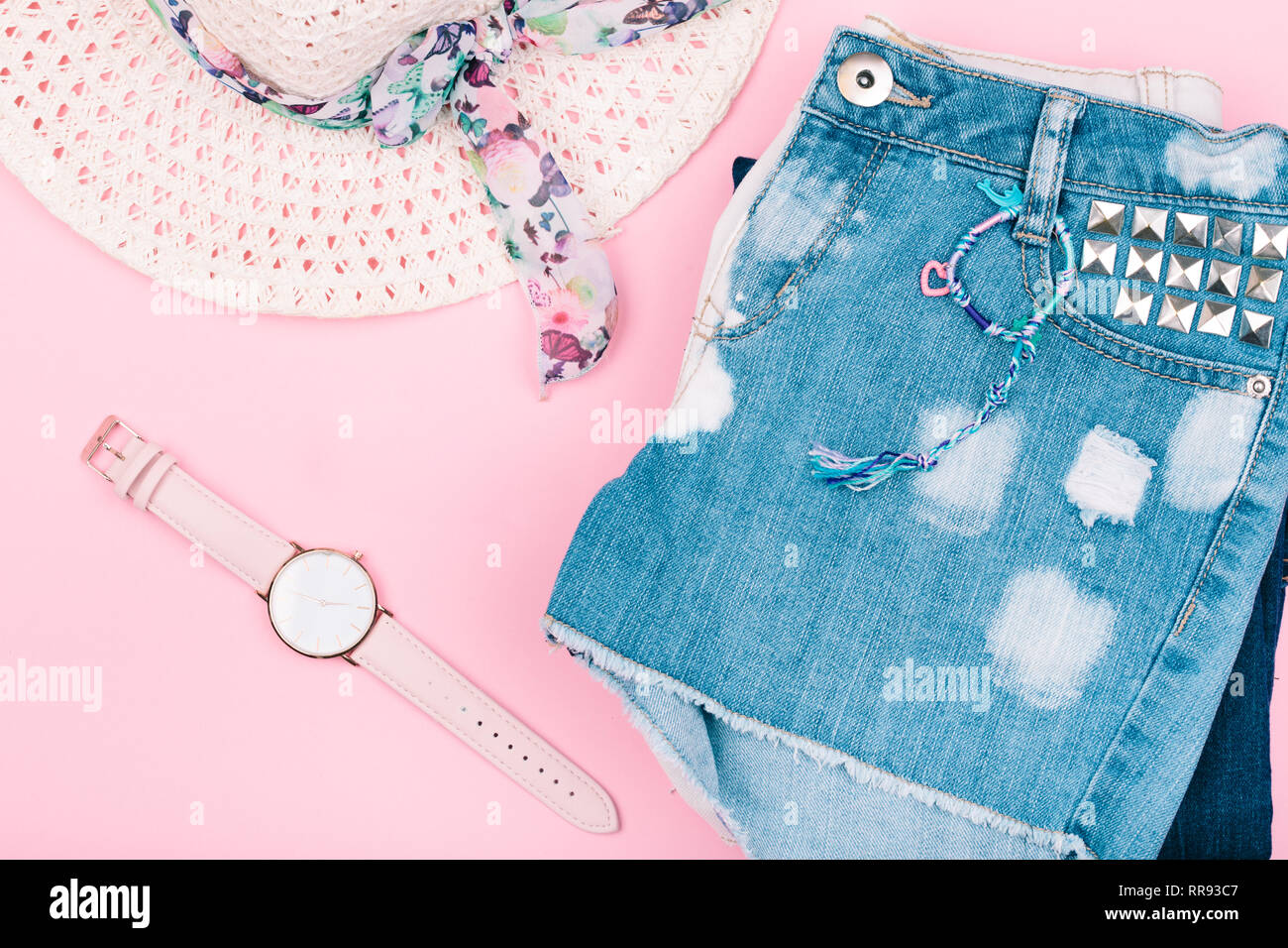 5da58ee90 Female girly clothes, blue jeans shorts, hat, watch on pink background
