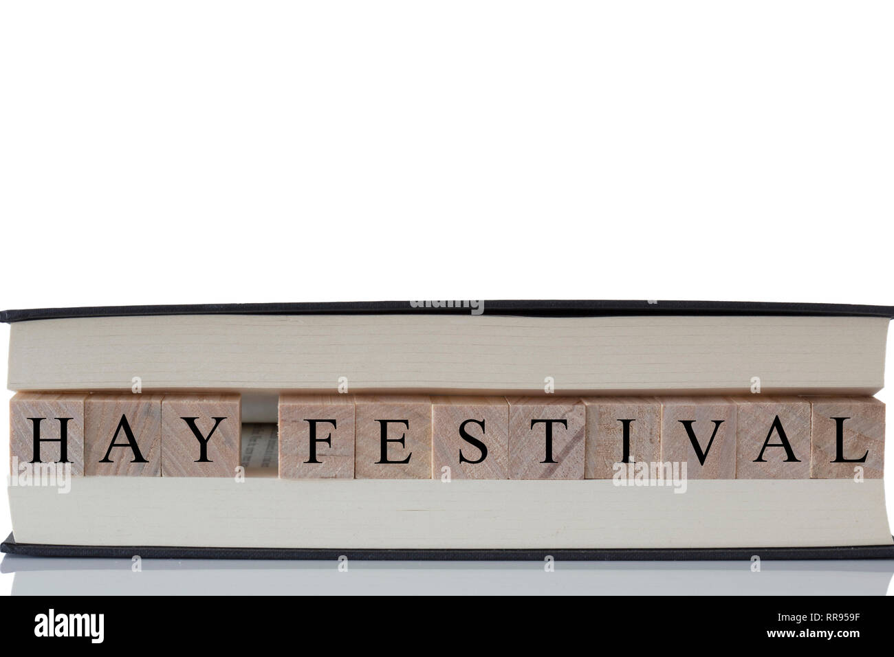 Hay Festival written on wooden blocks inside a book isolated on a white background with reflection - Stock Image