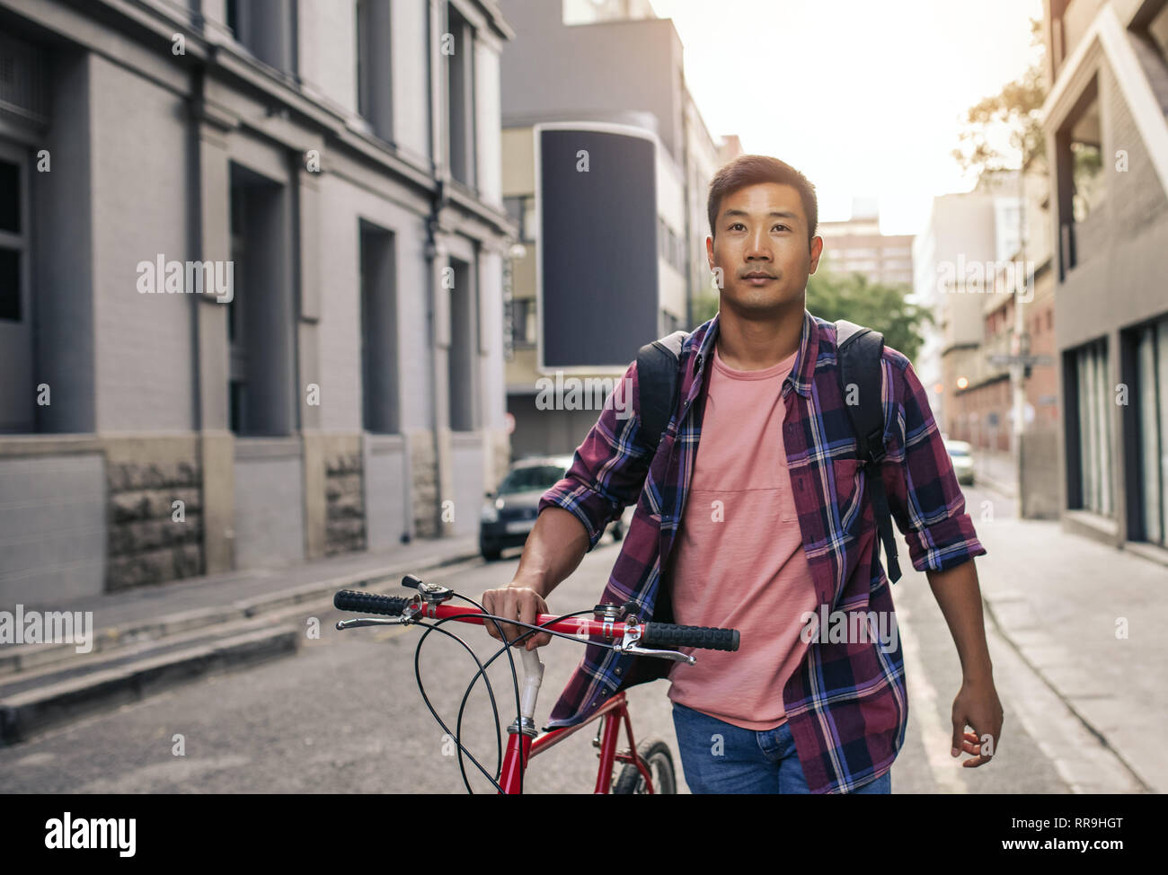 751e3cc97 Handsome Asian man walking with his bike through city streets - Stock Image