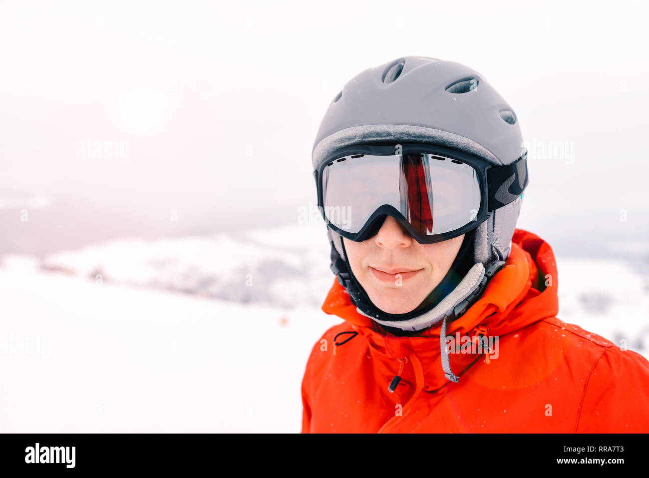 portrait of a skier woman in helmet and ski goggles with foggy mountains background - Stock Image