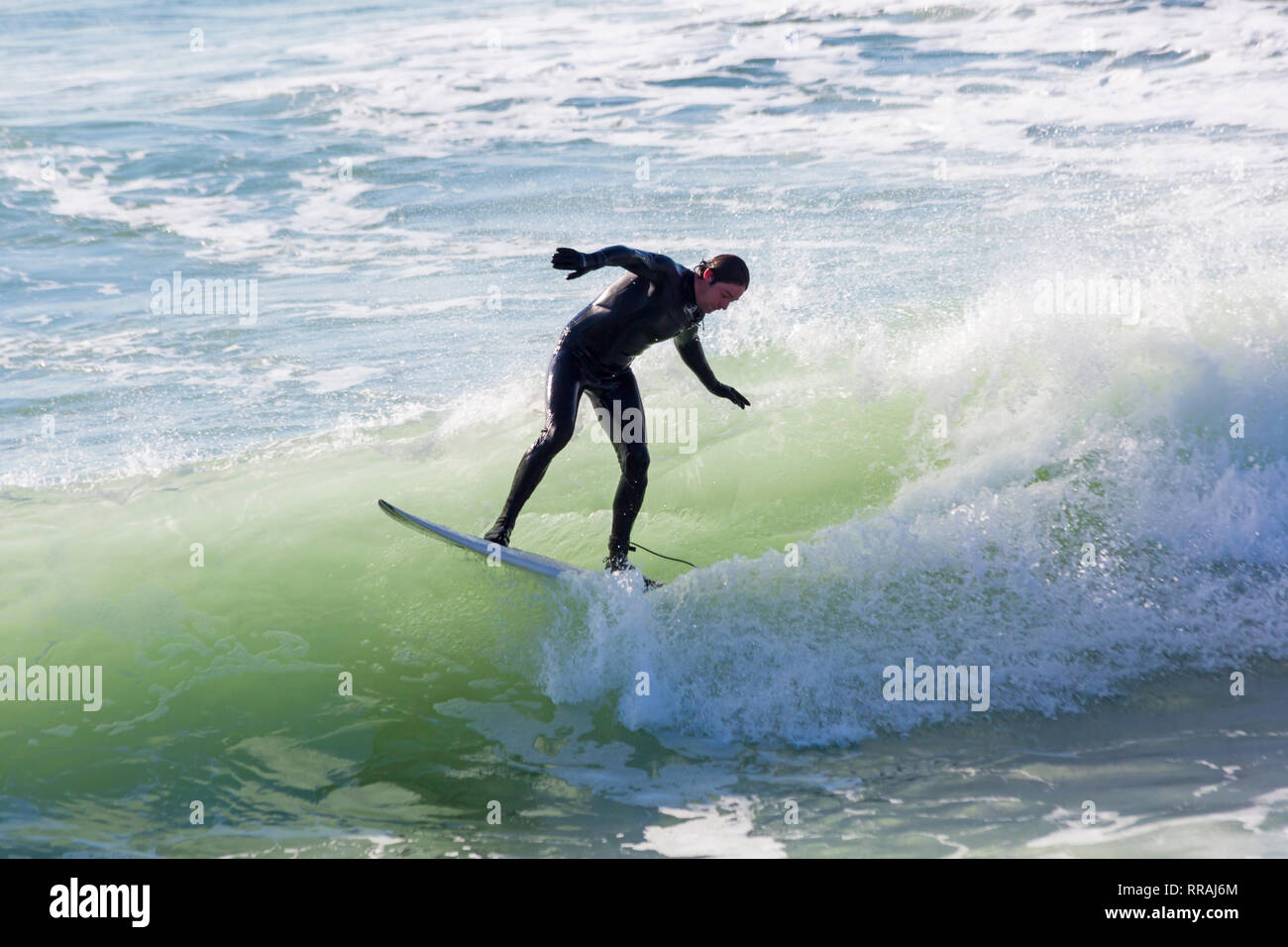 Bournemouth, Dorset, UK. 25th Feb, 2019. UK weather: big waves and plenty of surf create ideal surfing conditions for surfers at Bournemouth beach on a lovely warm sunny day expected to be the hottest day of the year and hottest February day ever.  Surfer on surf board riding the waves. Credit: Carolyn Jenkins/Alamy Live News - Stock Image