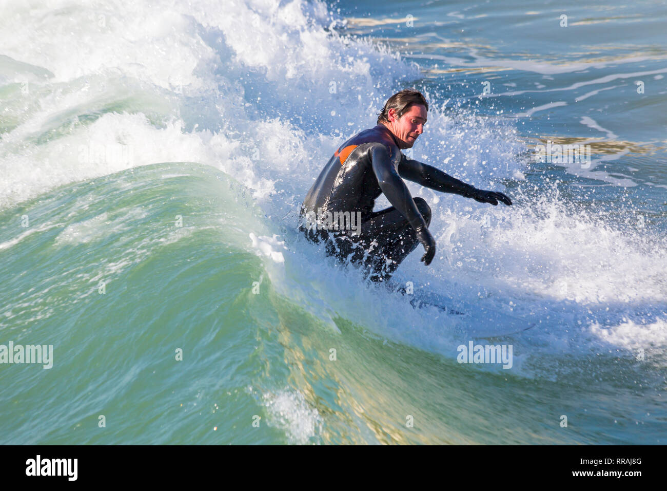 Bournemouth, Dorset, UK. 25th Feb, 2019. UK weather: big waves and plenty of surf create ideal surfing conditions for surfers at Bournemouth beach on a lovely warm sunny day expected to be the hottest day of the year and hottest February day ever. Surfer on surf board riding the wave. Credit: Carolyn Jenkins/Alamy Live News - Stock Image