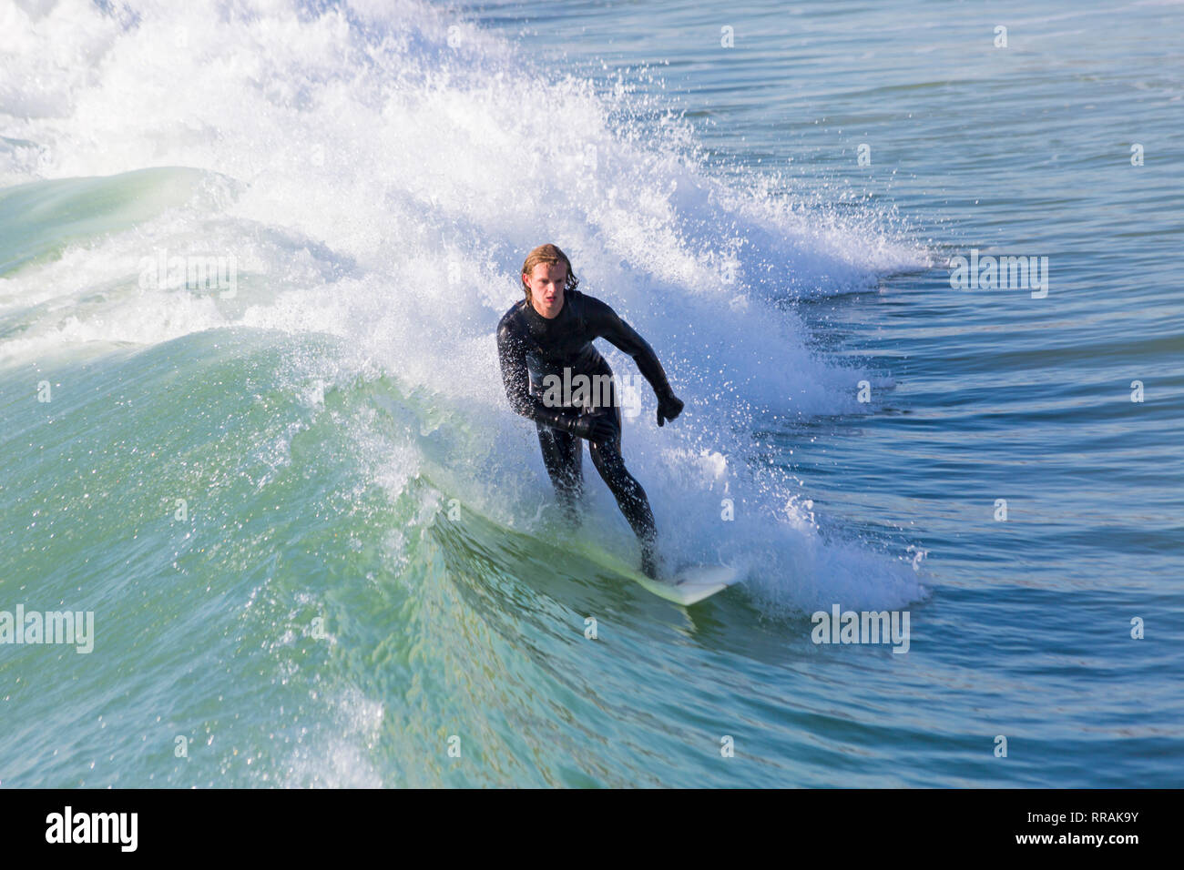Bournemouth, Dorset, UK. 25th Feb, 2019. UK weather: big waves and plenty of surf create ideal surfing conditions for surfers at Bournemouth beach on a lovely warm sunny day expected to be the hottest day of the year and hottest February day ever. Surfer riding the wave. Credit: Carolyn Jenkins/Alamy Live News - Stock Image