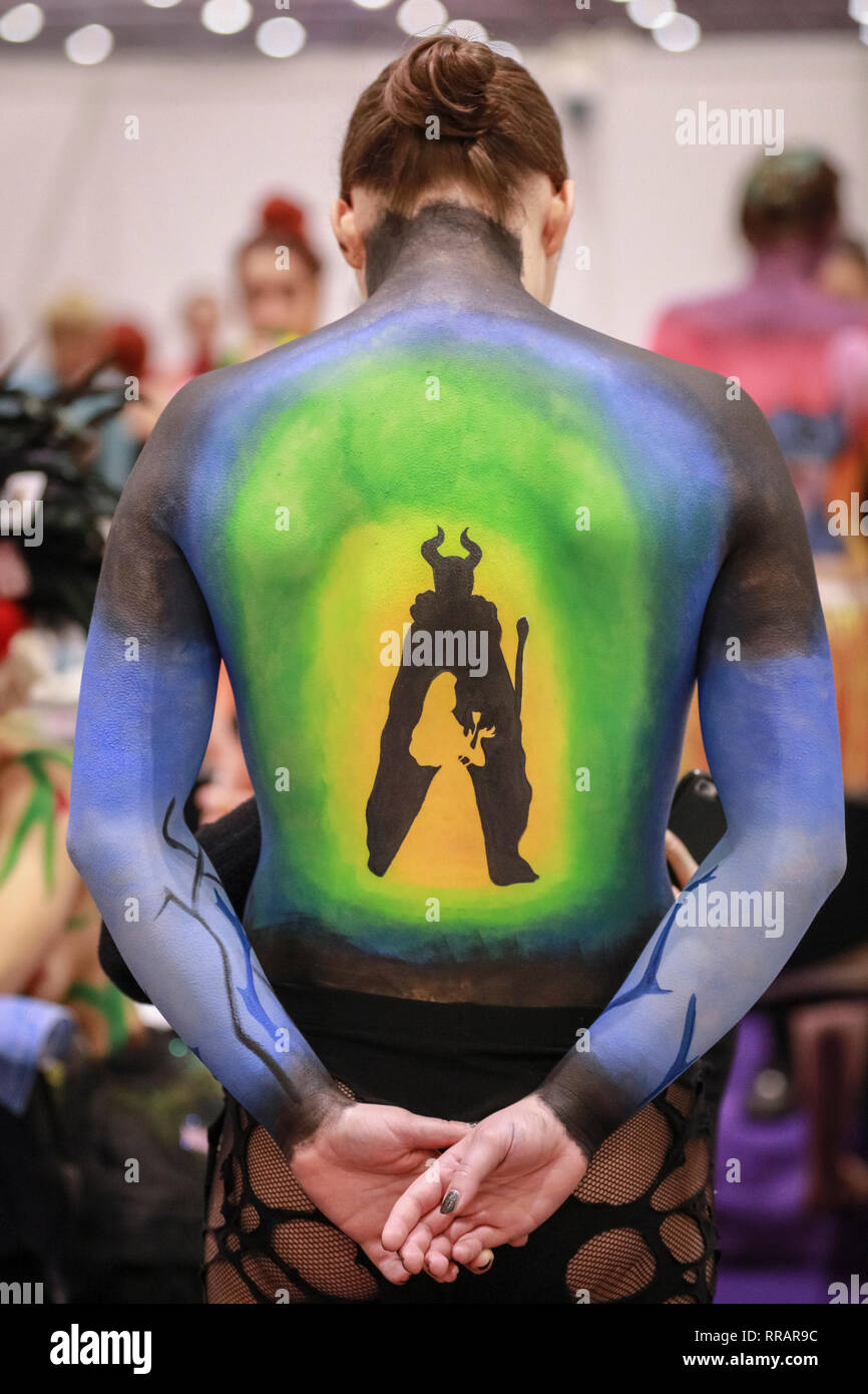 Excel, London, UK. 25th Feb, 2019. A Disney inspired motive painted on the model's back. A model with bodypaint, hair and makeup is prepared for the Warpaint Championships, held in different categories. The Professional Beauty London show brings together hair and beauty practitioners, cosmetics and aesthetics professionals, and representatives from over 800 brands with those interested in hair and beauty in the UK's biggest industry event at ExCel London Exhibition Centre. Credit: Imageplotter/Alamy Live News - Stock Image